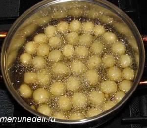 Шарики из картофельного теста кипят в раскаленном масле