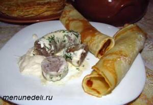 Колбаски в сметанном соусе порезанные кусочками и поданные с блинами