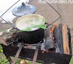 В кастрюле на открытом огне в куриный бульон добавлена зелень картофель и морковь