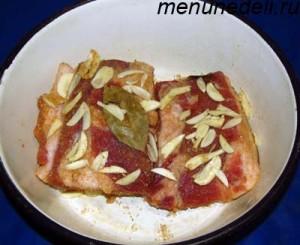 К кусочкам сала с солью и перцем добавляем порезанный чеснок и лавровый лист