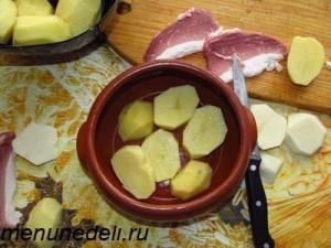 Крупно порезанный картофель выкладывается на дно горшочка