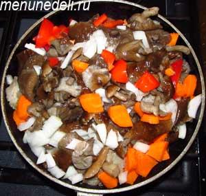 Грибы и порезанные кубиками морковь лук и болгарский перец тушатся на сковороде