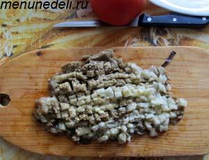 Очищенный и мелко порезанный запеченный баклажан на разделочной доске