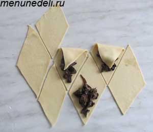 Тесто тонко раскатывается и разрезается на кусочки в виде ромбика сверху начинка