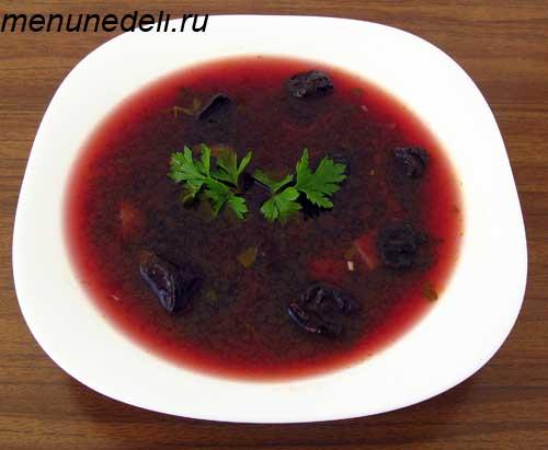 Темный борщ с грибами и черносливом на обед в тарелке