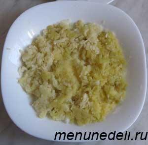 Натертый картофель выложенный на лук в тарелке