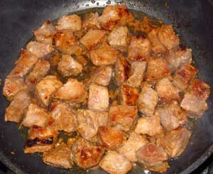 Свинина обжаривается на сковороде с разогретым кукурузным маслом