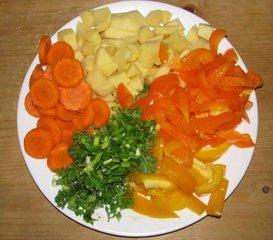 Мелко нарезанные морковь картофель болгарский перец  и зелень для супа