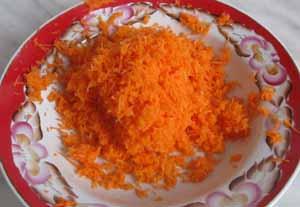Морковь натертая на мелкой терке в тарелке для приготовления салата