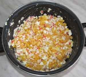 Готовый салат с крабовыми палочками и апельсинами в кастрюле