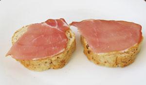 Ломтики копченой мясной нарезки на обжаренных тостах со сливочным маслом