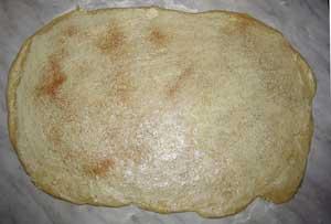 Раскатанное тесто смазано маслом и посыпано сахаром и корицей