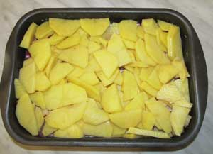 поверх свинины и яблок выложен порезанный картофель