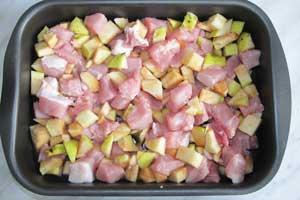 На дно противня выложены перемешанные свинина яблоки