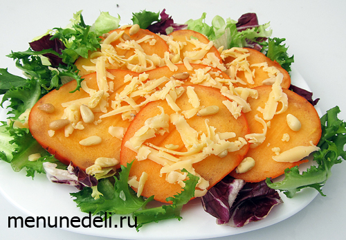 Салат с хурмой сыром и салатными листьями перед подачей на стол
