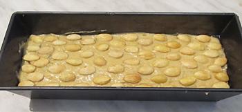 Тесто с цукатами выложенное в форму и миндаль сверху