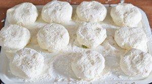 Шарики из сырного теста посыпанные мукой на разделочной доске