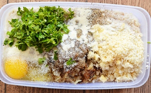 Смешанные в одной емкости куриный фарш мелко порезанная петрушка потертый сыр и яйцо