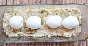 4 вареных яйца выложены на половину фарша в форме для запекания
