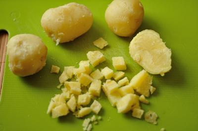 Отваренный в мундире очищенный и порезанный кубиками картофель