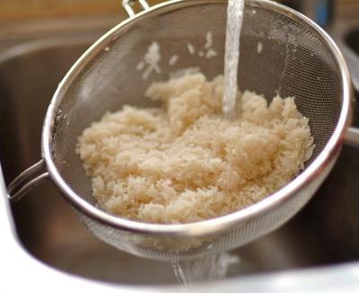 Рис промывается в дуршлаге под проточной водой