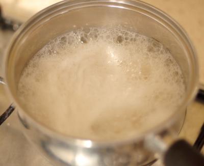 Вода с рисом в кастрюле доводится до кипения