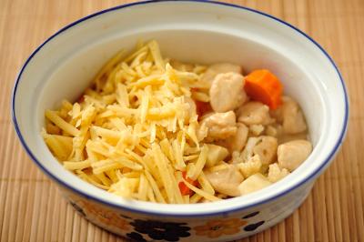 Слой курицы с овощами посыпан тертым сыром