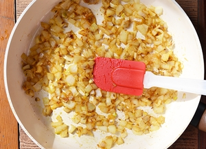 Лук обжаривается в сковороде со специями до золотистого цвета
