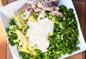 Порезанные ингредиенты соединенные с заправкой для салата
