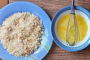 Панировочные сухари в тарелке и взбитое яйцо