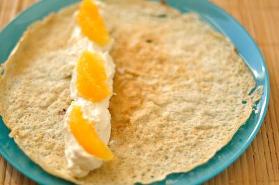 Начинка с кусочками апельсина выложена на блинчик