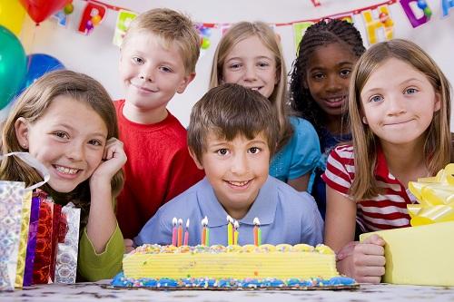 Мальчик задувающий свечки на торте на детском дне рождении