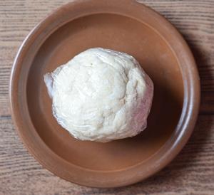 Сформированный из теста шар в пищевой пленке