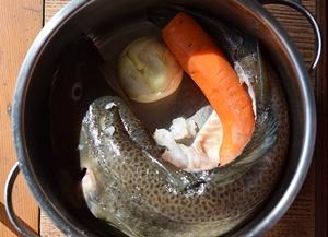 Выпотрошенная рыба с луком и морковью варится в кастрюле