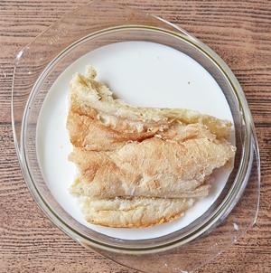 Ломтик хлеба замоченный в миске с молоком