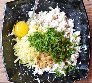 В одной миске собраны рыбное филе отварной картофель зелень жареный лук и яйцо
