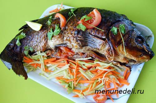 Целый карп, фаршированный черносливом и овощами на большом блюде