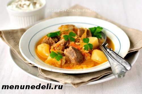 Готовый айнтопф из мяса свинины, картофеля и квашеной капусты на тарелке