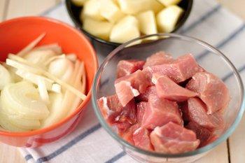 Нарезанные крупными кусочками мясо свинины лук и картофель для приготовления айнтопфа