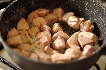 Процесс обжаривания свинины на сильном огне до румяной корочки в сковороде