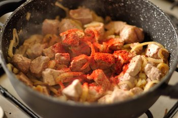Добавленное к луку мясо паприка и бульон тушатся в сковороде