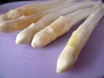 Хорошо помытые и почищенные головки белой спаржи на разделочной доске