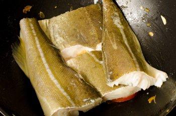 В немытую сковороду выложена рыба поверх помидоров порезанных полукольцами