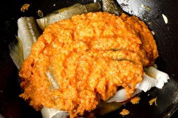 На рыбу в сковороде положено предварительно подготовленное пюре из помидоров, миндаля, лука и чеснока