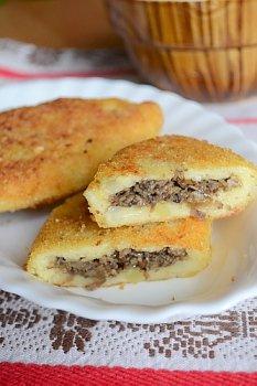 Картофельные зразы с грибами в разрезе и целиком на тарелке
