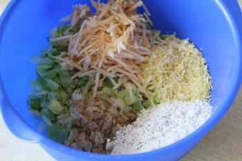 Смешанные в одной миске  измельченные капуста и яблоки лук сыр мука соль и перец