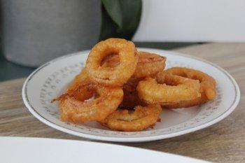 Красивые кольца лука в кляре на тарелке