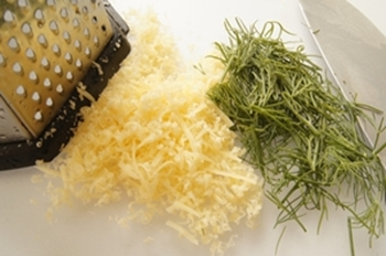Мелконатертый сыр и порезанная зелень для приготовления омлета
