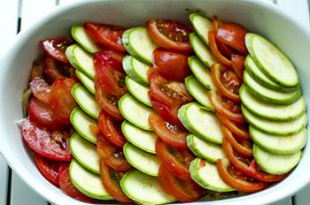 Порезанные тонкими ломтиками помидоры и кабачки выложены рядами внахлест