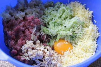В глубокой миске сложены все измельченные игредиенты фарш овсянка сыр яйцо и кабачок